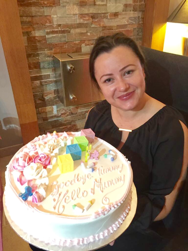 Lorne Park Dental assistant, Joanna holding baby shower cake and smiling